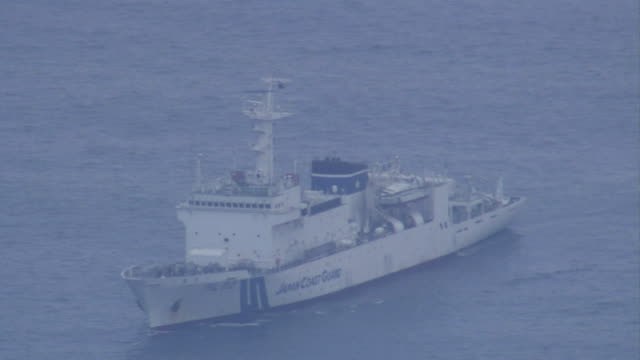 Aerial view Helicopter flying near Mount Shindake Japan Coast Guard ship in the middle of the ocean