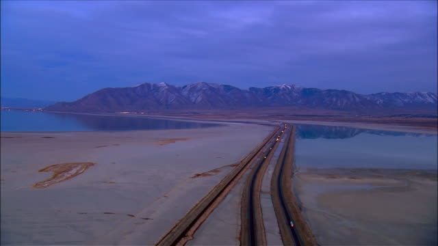 Aerial view I-80 running through the Great Salt Lake / mountains mirrored in surface of the water / Utah