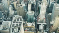 Aerial view looking  down at midtown Manhattan as helicopter flies right over Chrysler building NYC