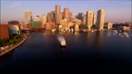 Aerial view low over water towards downtown / rising over cityscape / Boston, Massachusetts