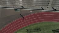 UHD 4K Antenne anzeigen: männlichen Sprinter training und sprinten auf der Spur