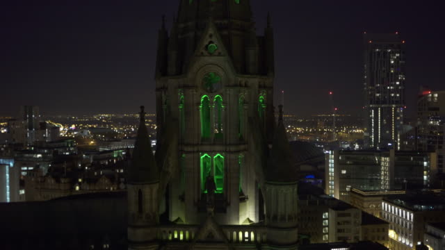 Aerial view Manchester at night, town Hall tower in foreground, city in background.