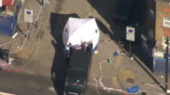 Aerial view of a body being moved from a forensic tent onto a police ambulance van at the scene of the Finsbury Park mosque attack