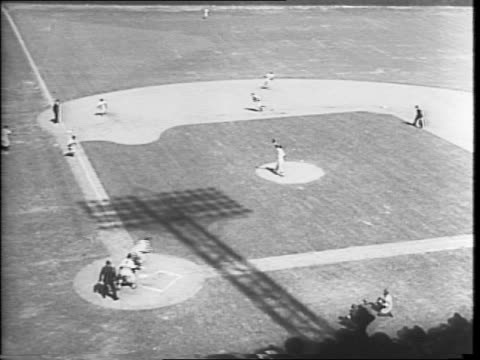 Aerial view of a tight crowd of people / marching band performing on a baseball stadium field / men raising the American flag in the baseball field /...