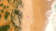 Aerial view of a woman alone in an amazing and unspoiled beach in the spain coast