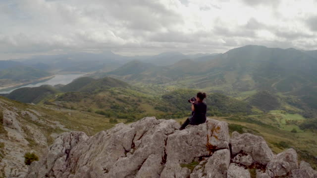 Aerial view of a woman taking pictures over a mountain