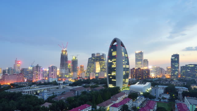 Aerial View of Beijing City Skyline and CCTV Headquarters, Day to Night Transition, Zoom