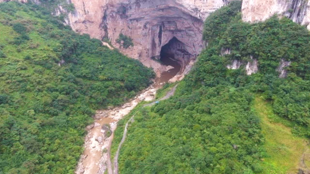 Aerial view of Big Cave Entrance on Cliff on Tropical Mountain, Guizhou Province, China