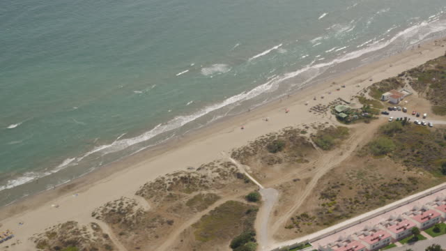 aerial view of coastline, beach, restaurants and hotel complexes