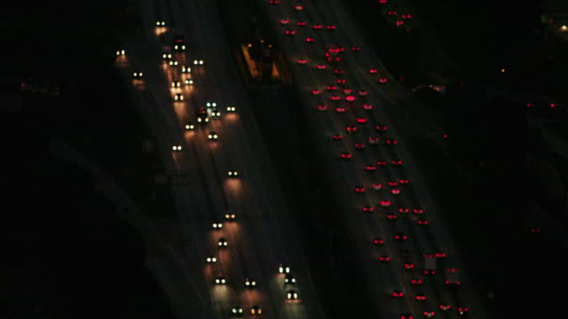 Aerial view of commuter traffic with lights on, racking focus, LA California