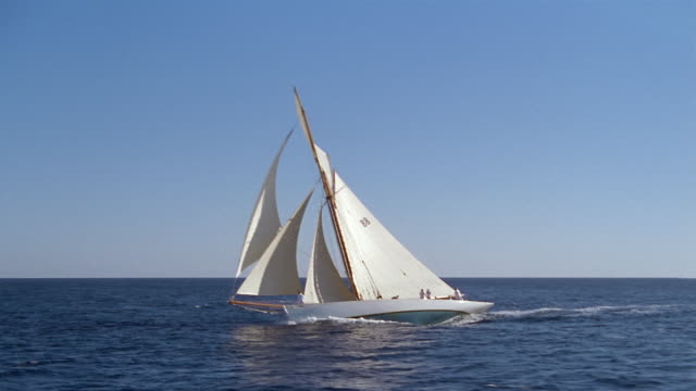 Aerial view of crew sailing yacht on ocean / boat leaning to the side