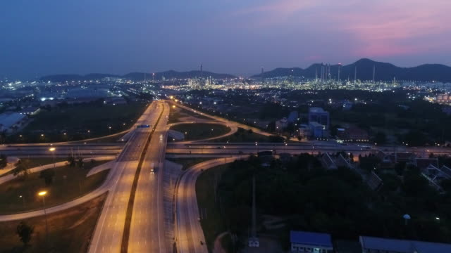 Aerial view of Highway traffic and Oil refinery at twilight time