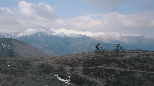 Aerial view of mountain bikers descending mountain ridge below snow capped mountains