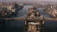 Aerial view of Queensboro Bridge and Roosevelt Island flying over East river, NYC