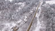 4K Aerial view of road in snow mountain
