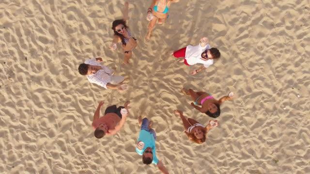 4K Aerial view of seaside and friends drinking beer on beach