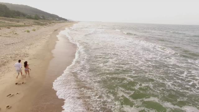 4K Aerial view of seaside and running people