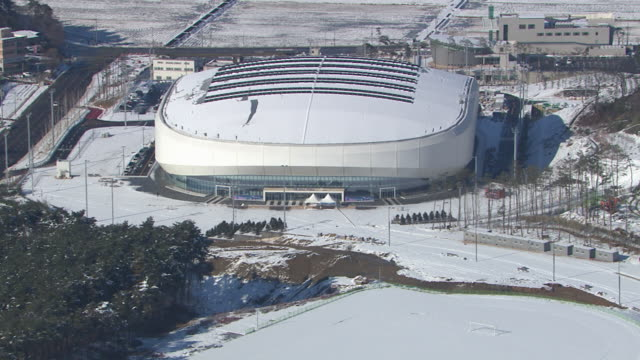 Aerial view of snow-covered Entrance of Ice Arena in distance (Stadium for 2018 Winter Olympics)