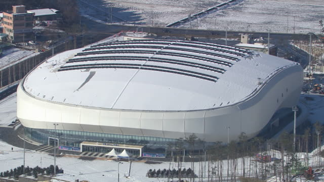 Aerial view of snow-covered Ice Arena in distance (Stadium for 2018 Winter Olympics)