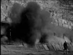 Aerial view of strip mine in Utah / People look out from observation deck / Man pumps explosives detonator / hillside explodes while man in...