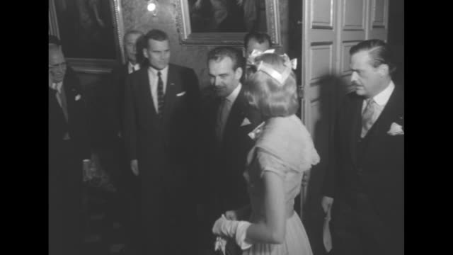 Aerial view of the principality of Monaco / Grace Kelly and Rainier entering room / the couple meets diplomats / closer view of the couple / Rainier...