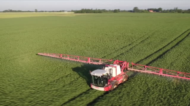 Aerial view of tractors spraying pesticide on crops