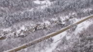 4K Aerial view of traffic in snow mountain
