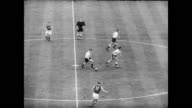 Aerial view of Wembley Stadium packed with fans / Queen Elizabeth arrives at the match and takes a seat / kick off / several goals scored / huge...
