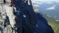 Aerial view of wingsuit flyers jumping from cliff