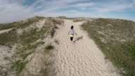 Aerial view of woman running through sandy dune area