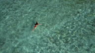 Aerial (drone) view of woman swimming in clear ocean water