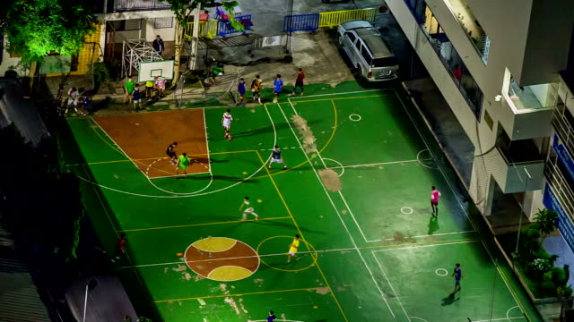 Aerial view of young boys playing football at small court