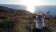 Aerial view of young woman arms outstretched on mountain
