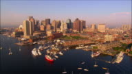 Aerial view over boats in the inner harbor w/ downtown skyline in background / over bridges crossing Fort Point Channel / Boston, Massachusetts