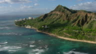 Aerial view over Diamond Head Lighthouse on the coast of Honolulu with distant skyscrapers.