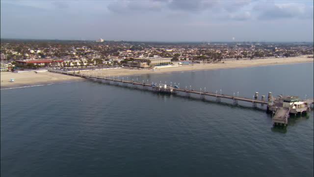 Aerial view over Long Beach Pier past beach / Long Beach