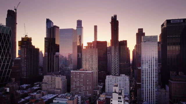 Aerial View Over Manhattan with Rising Sun Between Skyscrapers