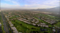 Aerial view over residential neighborhoods and golf courses with mountains in background / Palm Springs, California