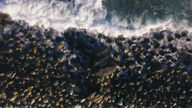 Aerial view over waves breaking on a rocky shore
