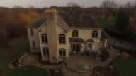 Aerial view rising over large white house in Chicago suburb in autumn