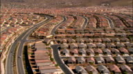 Aerial view streets running through rows of tract housing with hills in background / Las Vegas, Nevada