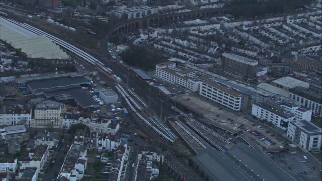 Aerial views of a Southern Rail train pulling into Brighton Station and the surrounding area including the coast East Sussex UK