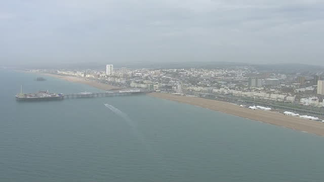Aerial views of Brighton Beach with the remains of the West Pier and Brighton Pier with signs of Air Pollution on April 10 2015 in Brighton England
