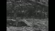 VS aerial views of vast wrecked Mitsubishi manufacturing plant in Nagoya Japan / pan skeletons smokestacks of destroyed buildings collapsed girders...