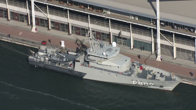 Aerial views warship and gunboats moored alongside the Excel Centre