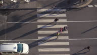 4K | Aerial wide angle shot of a crosswalk. Fluid traffic in this intersection of Madrid. Pedestrians cross the street. We can see the afternoon lateral shadows of the people and the cars.