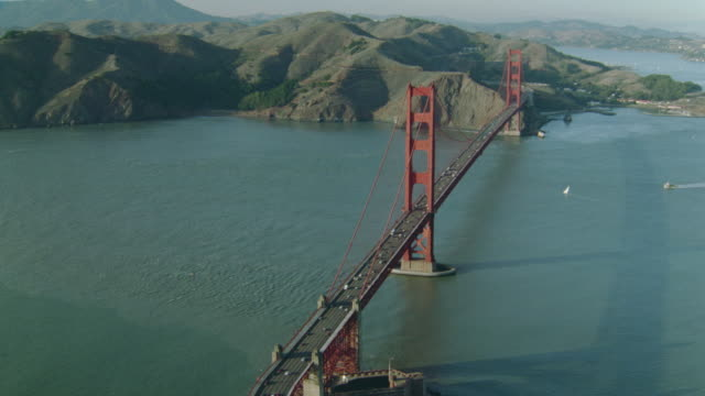 Aerial wide shot around Golden Gate Bridge with traffic / Marin Headlands in background / San Francisco, California