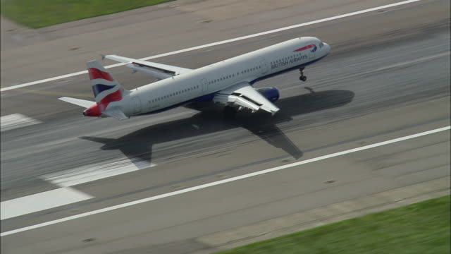 Aerial wide shot British Airways jet landing at Heathrow Airport / zoomout greater airport area / London, England