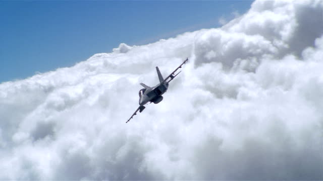 Aerial wide shot F/A-18 Super Hornet soaring over clouds / slowing down and hovering in front of CAM