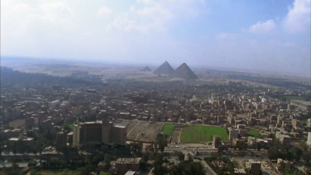 Aerial wide shot Giza Pyramids and downtown cityscape / Cairo, Egypt